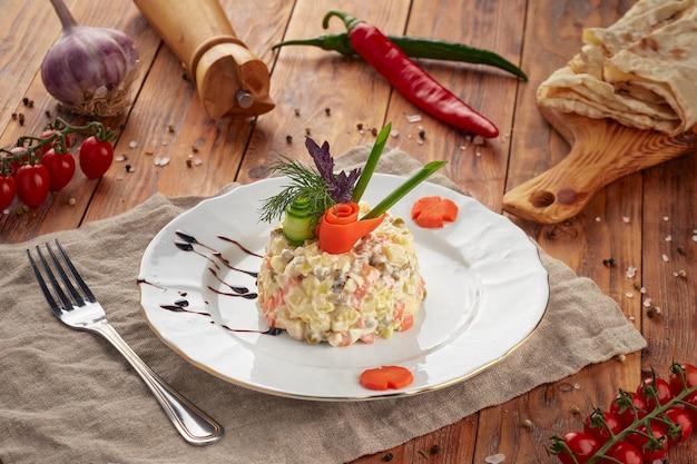 Insalata tradizionale russa olivier con carne e verdure su un fondo di legno
