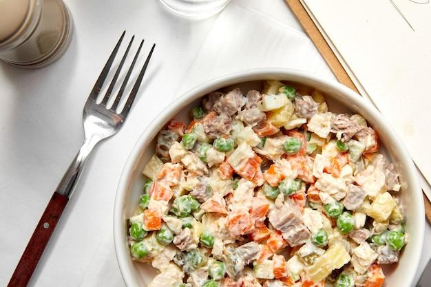 Insalata tradizionale russa olivier con verdure e carne.