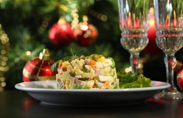 Insalata tradizionale russa olivier, su tavola di legno, su sfondo luminoso