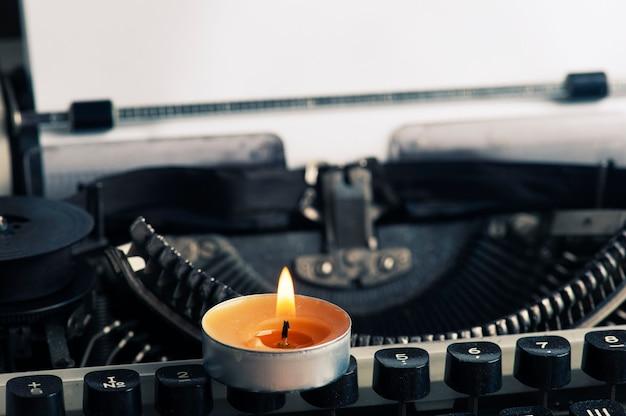Macchina da scrivere russa close up e fiori secchi con candela aromatica accesa. concetto di san valentino, carta kraft e tonica vintage