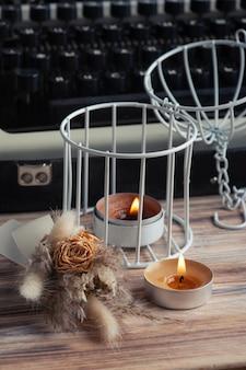 Macchina da scrivere russa close up e fiori secchi con candela aromatica accesa. carta kraft e dai toni vintage
