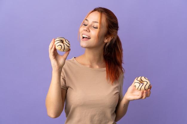 Donna russa isolata su ciambelle viola della holding con l'espressione felice