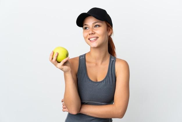 Donna russa isolata su bianco con una mela e felice
