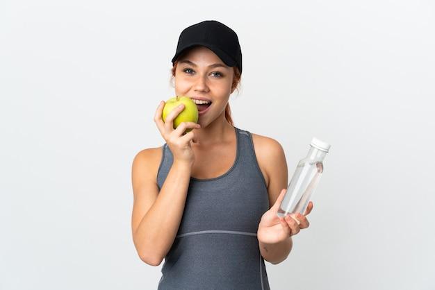 Donna russa isolata su bianco con una bottiglia d'acqua e mangiare una mela