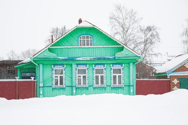 Una casa di legno russa coperta di neve