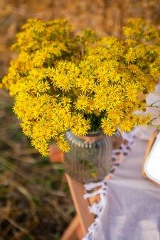 Bouquet rustico di fiori gialli in un vaso di vetro con balle di paglia sullo sfondo