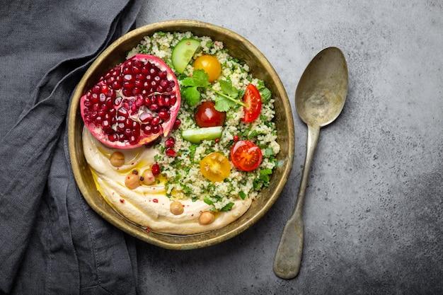 Ciotola rustica con insalata di cous cous con verdure, hummus e melograno appena tagliato. pasto in stile mediorientale o arabo con condimenti e coriandolo fresco. bella e sana cena mediterranea