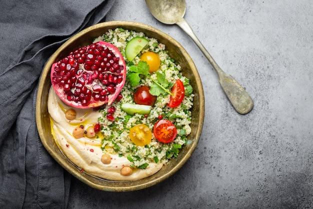 Ciotola rustica con insalata di cous cous con verdure, hummus e melograno appena tagliato. pasto in stile mediorientale o arabo con condimenti e coriandolo fresco. cena sana mediterranea, spazio per il testo