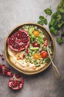 Ciotola rustica con insalata di cous cous con verdure, hummus e melograno appena tagliato. pasto in stile mediorientale o arabo con condimenti e coriandolo fresco. cena sana mediterranea, immagine tonica