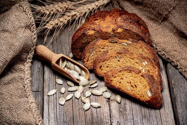 Pane rustico con zucca e semi di zucca su un vecchio tavolo in legno.