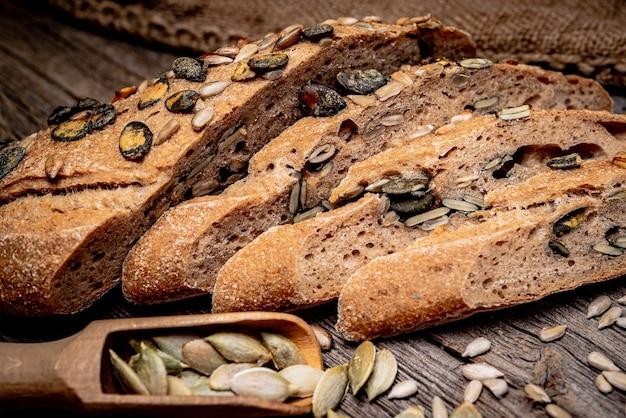 Pane rustico con semi di girasole e semi di zucca su un vecchio tavolo in legno.