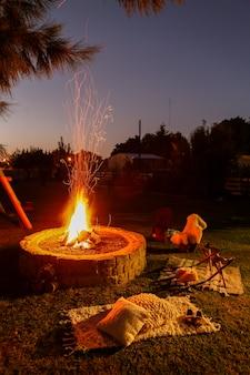 Fuoco di accampamento rustico e sedie intorno nel giardino di notte