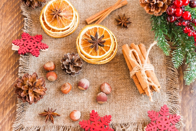 Composizione rustica in natale - ramo di abete rosso con bacche e coni, fette di arancia essiccate, noci, onis su tela. vista dall'alto.