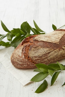 Pane scuro rustico su un tavolo bianco con rami di foglie