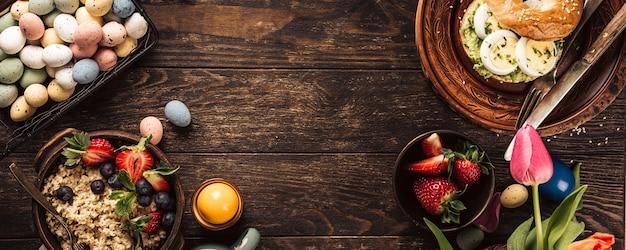 La prima colazione rustica di pasqua giaceva con uova bagel, tulipani, croissant, uova, farina d'avena con frutti di bosco, uova di quaglia colorate e decorazioni per le vacanze primaverili. vista dall'alto, copia dello spazio