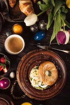 La prima colazione rustica di pasqua giaceva con uova bagel, tulipani, croissant, uova, farina d'avena con frutti di bosco, uova di quaglia colorate e decorazioni per le vacanze primaverili. vista dall'alto