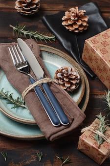 Tavola festiva rustica messa sulla tavola di legno con scatole regalo avvolte e pigne
