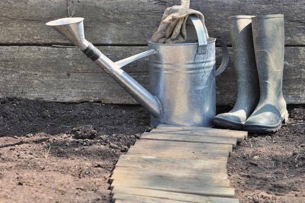 Candela di irrigazione in metallo rustico e stivali di gomma sul terreno