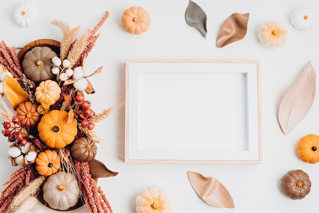 Mockup rustico con cornice vuota e decorazione della tavola autunnale. arredamento floreale per le vacanze autunnali con zucche fatte a mano. biglietto di auguri per le vacanze. flatlay, vista dall'alto