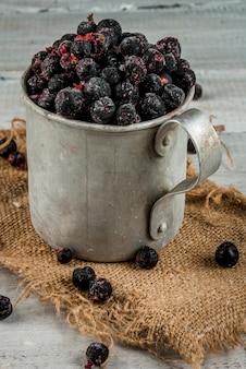 Vecchia tazza rustica con mirtilli e ribes congelati