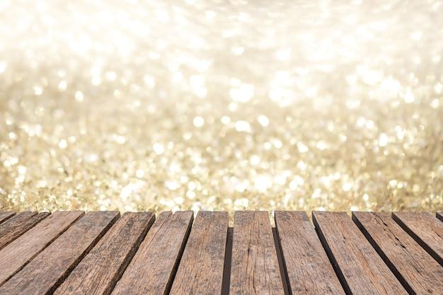 Tavolo in legno vecchio rustico davanti a luci bokeh brillanti argento e oro