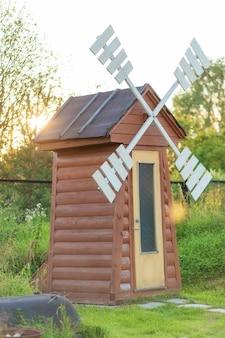 Toilette rustica all'aperto a forma di mulino a vento.
