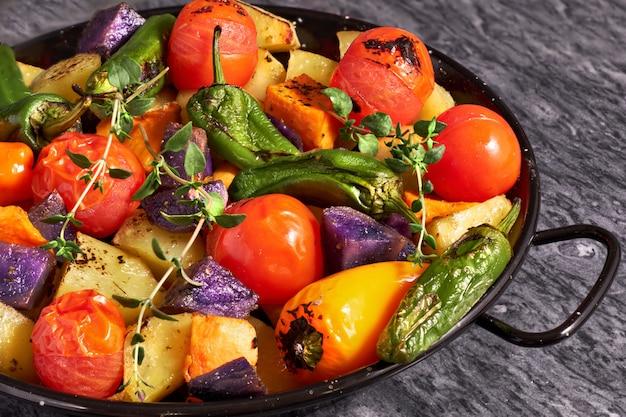 Verdure al forno del forno rustico nel fondo di pietra grigio di raggiro nero del piatto di cottura. pasto vegano vegetariano stagionale