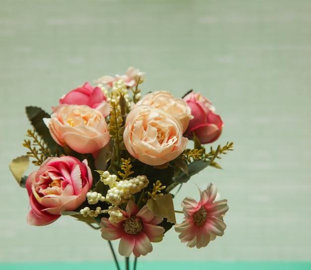 Foto rustica di un mazzo di fiori di peonie bianche e rosa su uno sfondo colorato vista frontale