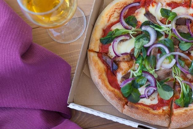 Pizza rustica con salame, mozzarella, olive e basilico vista dall'alto con copia spazio.