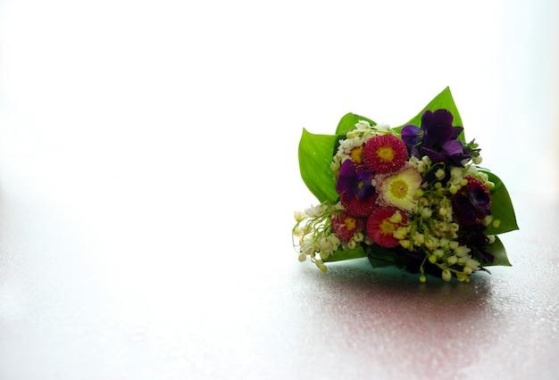 Rustico bouquet primaverile di fiori di bosco estivi su uno sfondo di vetro