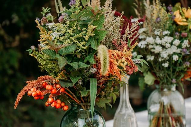 Mazzi di fiori in stile rustico sulla tavola in vasi e barattoli di vetro