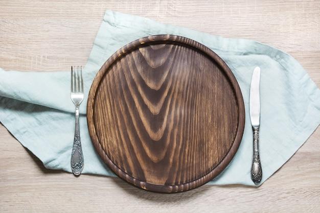 Tavolo rustico con piatto in legno e tovaglioli