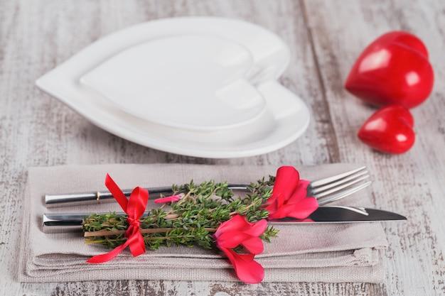 Tavola rustica con fiori di timo e ciclamino e decorazione a forma di cuore su tavola di legno chiaro con copyspace