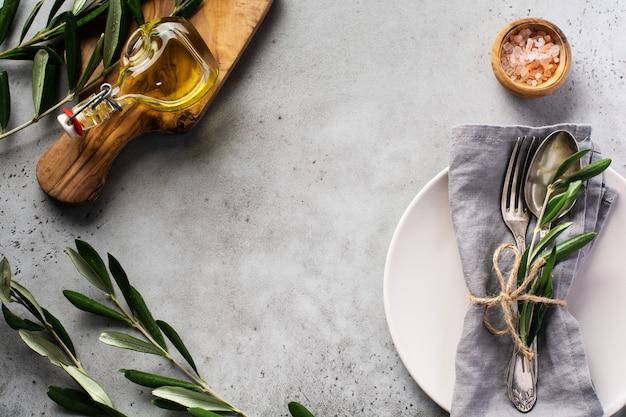 Set di posate vintage rustico. piastra con tovagliolo di lino grigio, forchetta e cucchiaio, ramo di ulivo su vecchio grigio cemento rustico. impostazione della decorazione della tavola per le vacanze autunnali.