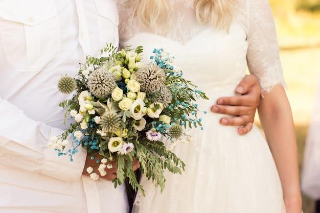Bouquet da sposa rustico in una tavolozza di colori turchese chiaro e brillante in una giornata di sole estivo.