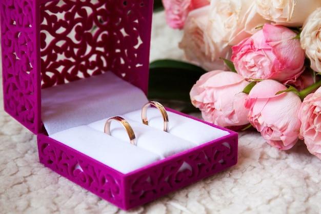Bouquet da sposa rustico e anelli nella casella su un divano di lusso
