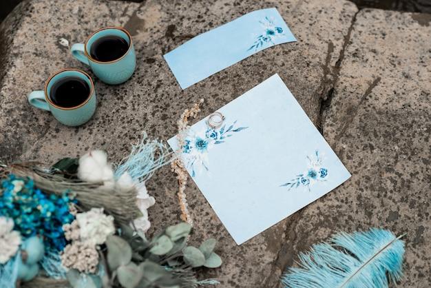 Carta di invito matrimonio rustico, sigillo di cera, vaso, pietra di mare, fiori Foto Premium