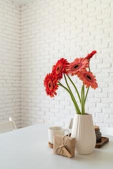 Muro di mattoni bianchi rustici con fiori di gerbera fresca rossa in un vaso bianco