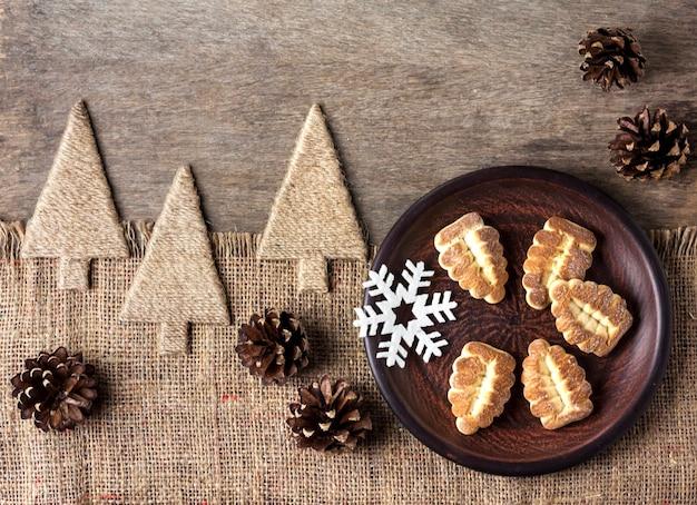 Composizione invernale rustica con biscotti di pasta frolla su un piatto e pigne Foto Premium