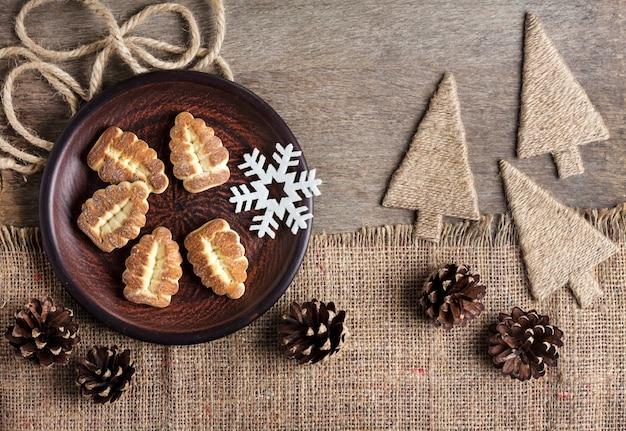 Composizione invernale rustica con biscotti di pasta frolla su un piatto e pigne