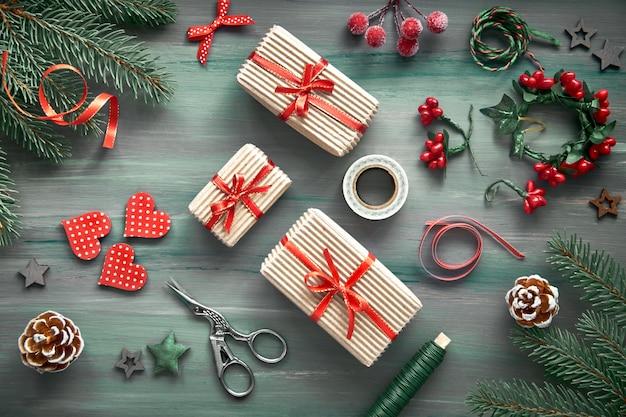 Fondo di legno rustico in verde e rosso con abete, regali di natale avvolti e decorazioni natalizie