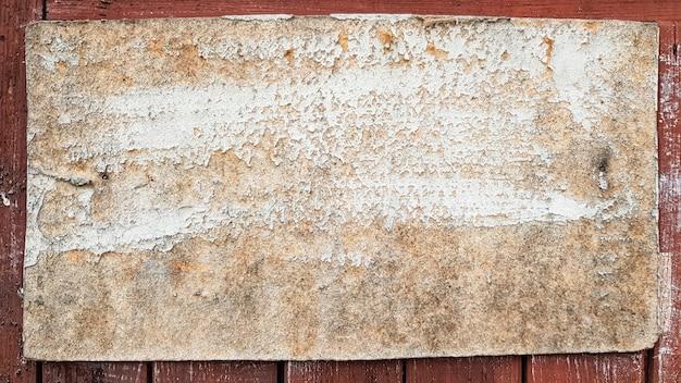 Un cartello in legno rustico su una tavola stagionata attaccata a una staccionata in legno. cornici d'epoca sulla vecchia parete in legno. struttura di legno grigia del fondo con lo spazio della copia. tavolo in legno da parete.