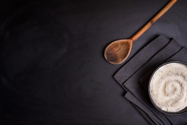Cucchiaio di legno rustico, ciotola nera con farina su uno sfondo di lavagna nera.