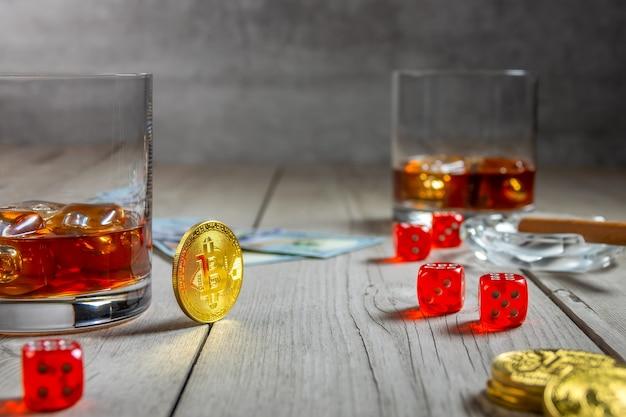 Tavolo in legno rustico. due bicchieri di whisky con cubetti di ghiaccio e un sigaro in un portacenere. dadi e banconote da un dollaro. poche monete bitcoin