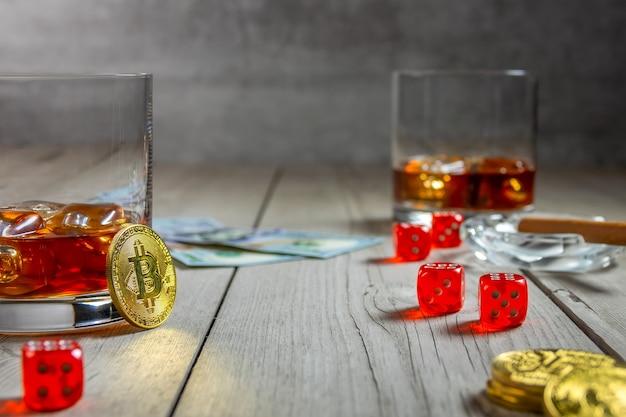 Tavolo in legno rustico. due bicchieri di whisky con cubetti di ghiaccio e un sigaro in un portacenere. fatture del dollaro e dadi. alcune monete bitcoin