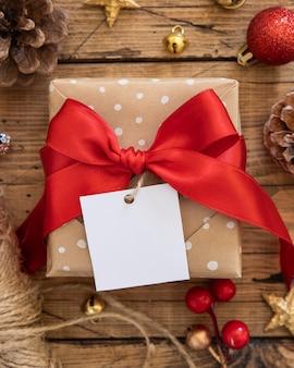 Confezione regalo avvolta rustica con etichetta regalo di carta su un tavolo di legno marrone con decorazioni natalizie rosse e dorate intorno alla vista dall'alto. composizione invernale con etichetta regalo quadrata vuota mockup, copia spazio