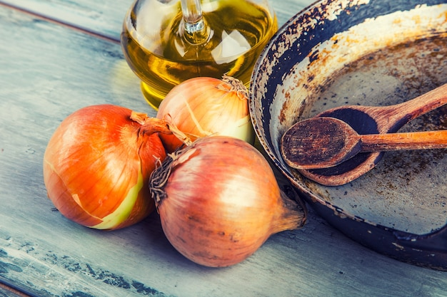 Concetto rustico costituito da una vecchia padella con cucchiai di legno posata su un tavolo di legno con cipolla e olio.