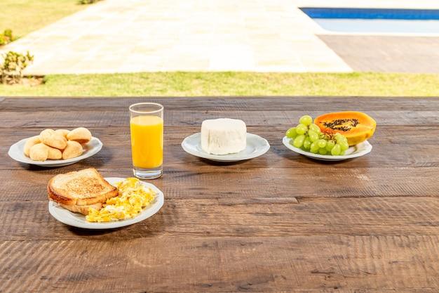 Tavolo in legno rustiica, con colazione. piatti bianchi con pane tostato e uova, un bicchiere di succo d'arancia, formaggio fresco e papaia e uva verde.