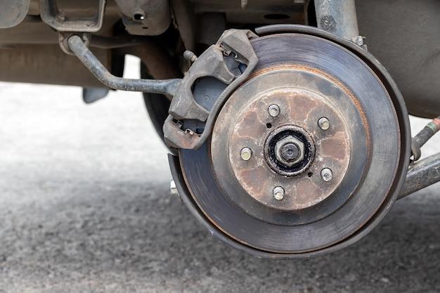 Mozzo arrugginito della ruota posteriore dell'auto con disco del freno al negozio di pneumatici