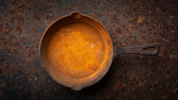 Padella in ghisa arrugginita su uno sfondo di texture di piastra metallica arrugginita sporca in rapporto hd completo, vista dall'alto